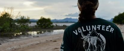 A volunteer in Thailand watches the sun set on a beach where she did conservation work.